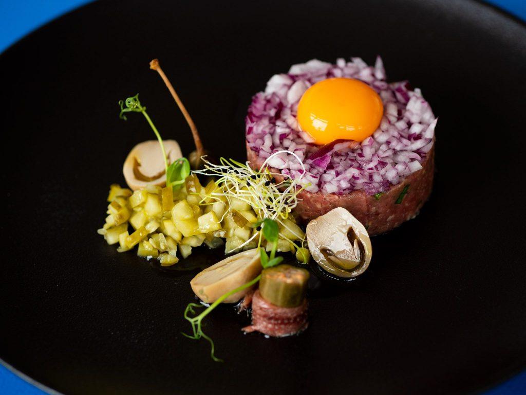 Na zdjęciu widać talerz, na którym ułożona jest porcja tatara z żółtkiem i różnymi dodatkami.