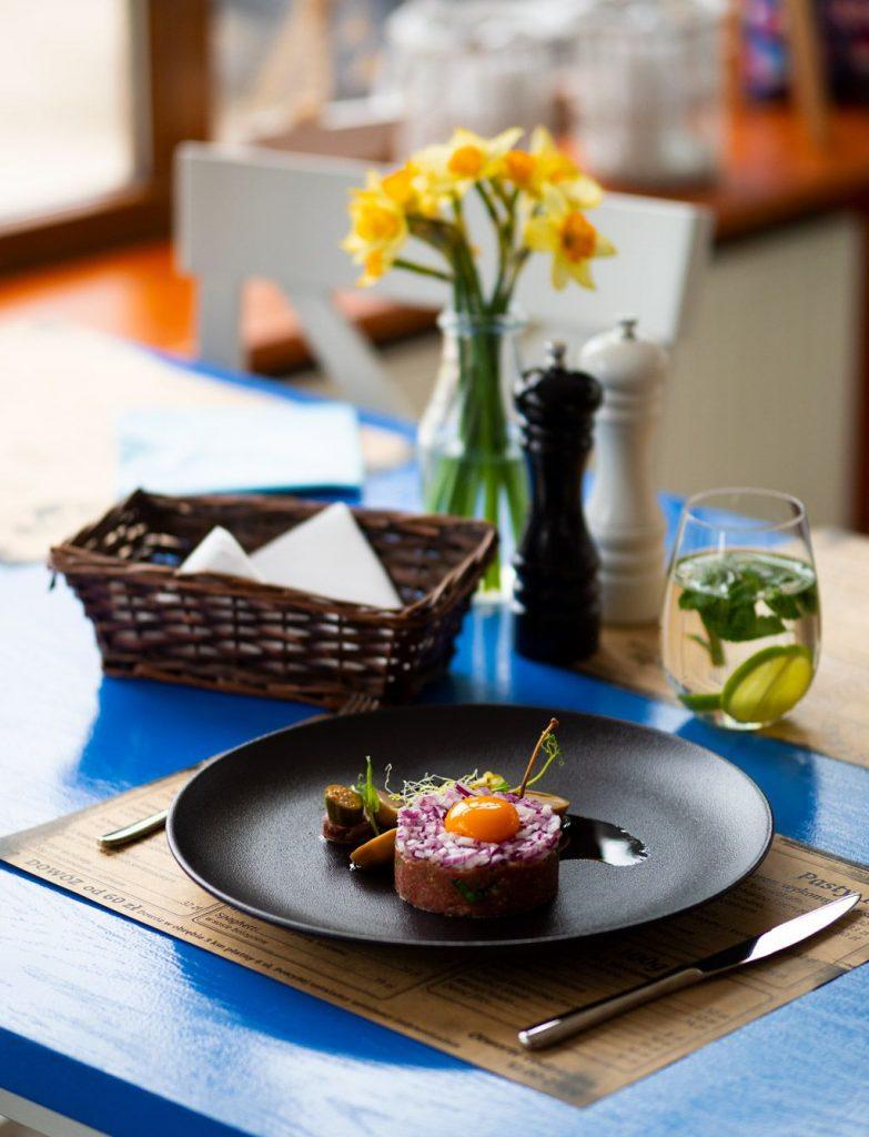 Na zdjęciu widać fragment stołu restauracji. Na stole stoi talerz w porcją tatara, obok niego szklanka z napojem, koszyczek ze sztućcami, wazonik ze świezymi kwiatami, solniczka i pieprzniczka.