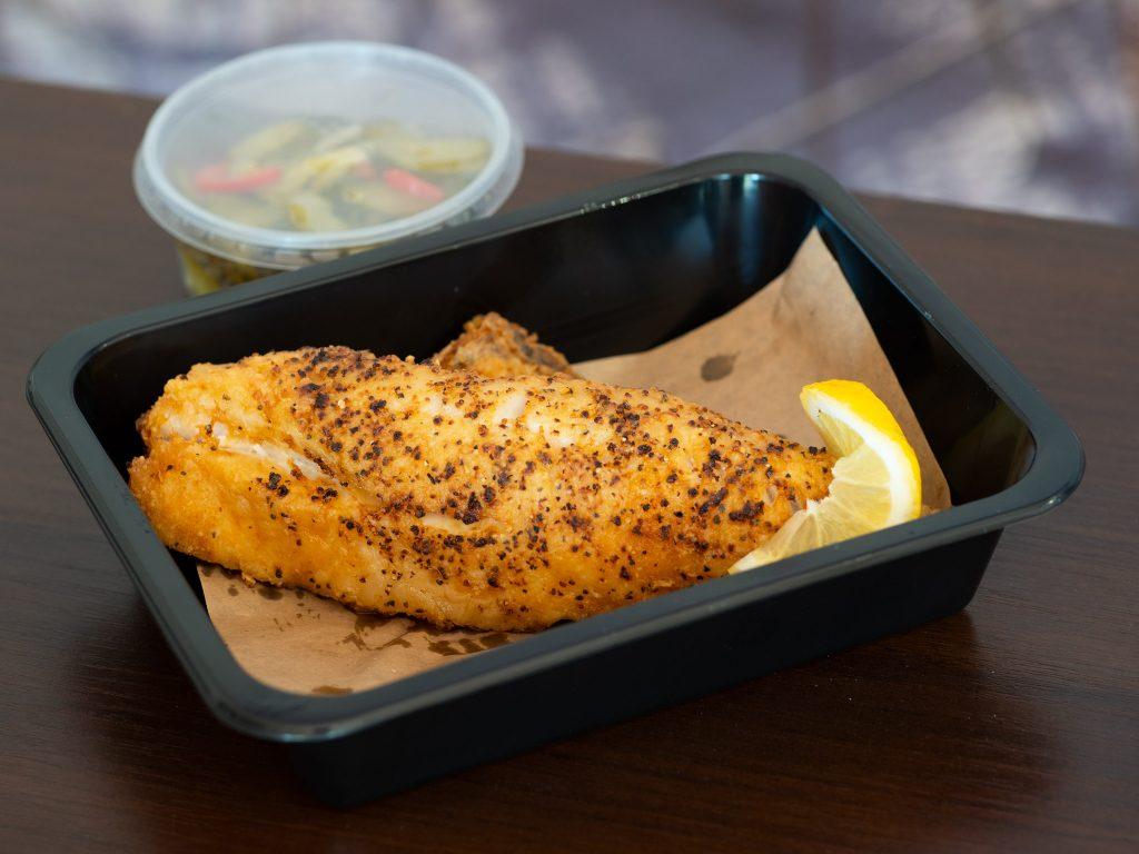 Zdjęcie przedstawia panierowaną porcję ryby zapakowaną w pudełko na wynos.