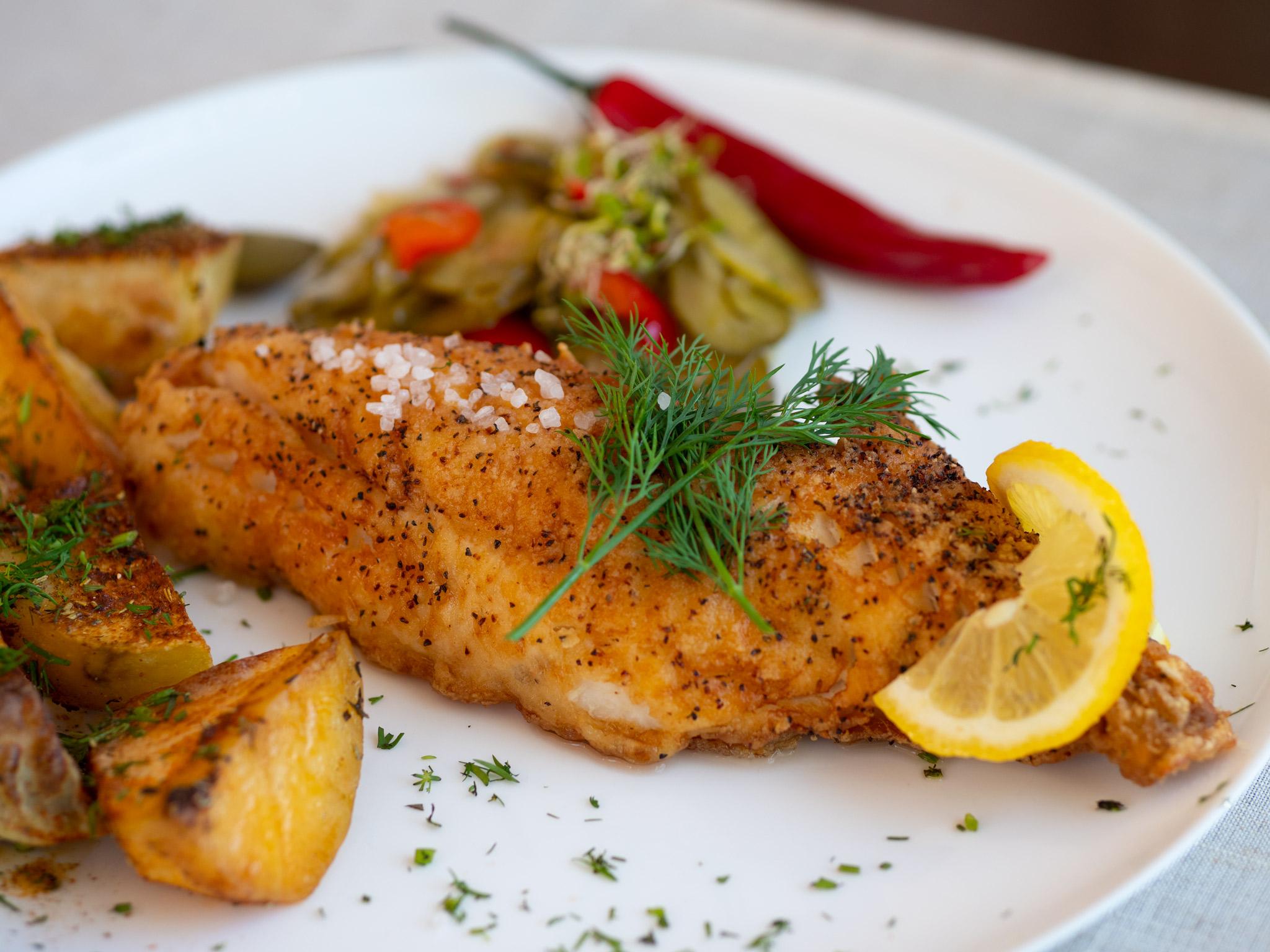 Na zdjęciu widać porcję smażonej ryby z opiekanymi ziemniakami.