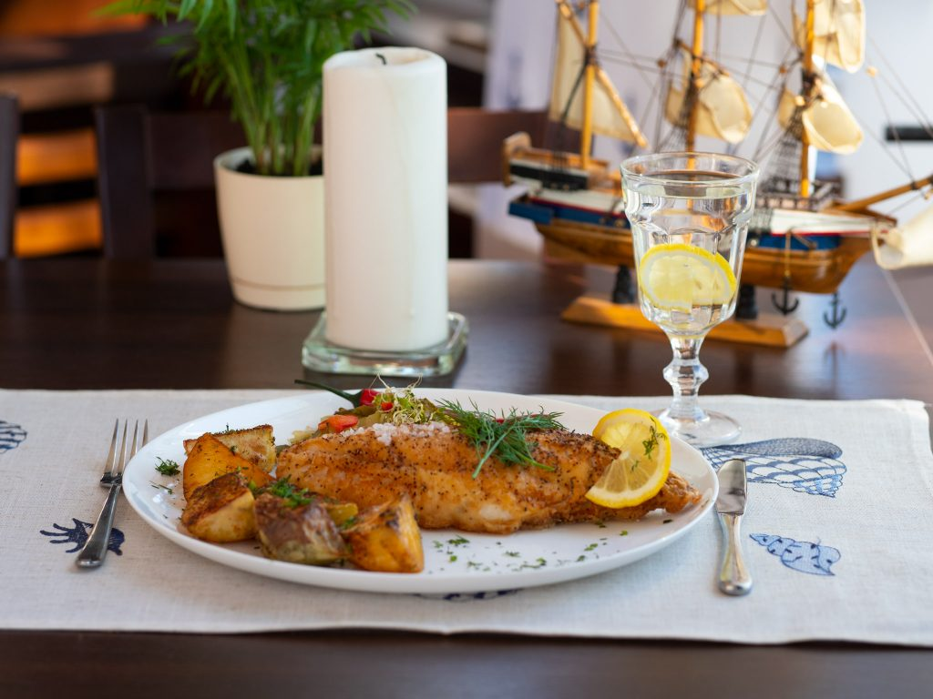 Na zdjęciu widać zastawiony stół i talerz z porcję ryby.