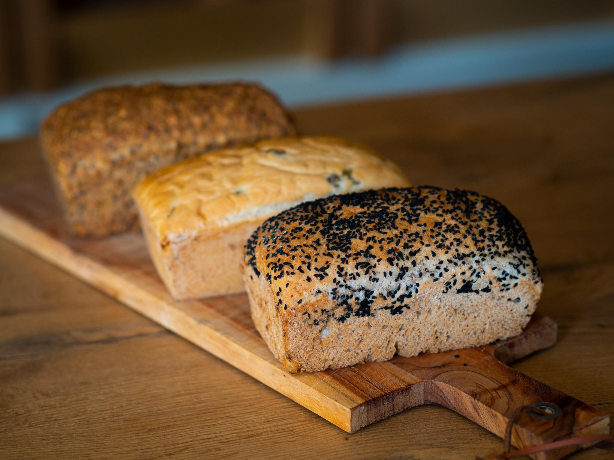 Na zdjęciu widac trzy bochenki chleba ułożone na drewnianej desce.