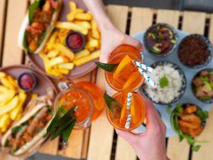Na zdjęciu widać stół w restauracji z jedzeniem i ręce wznoszące tost szklankami z koktajlami.