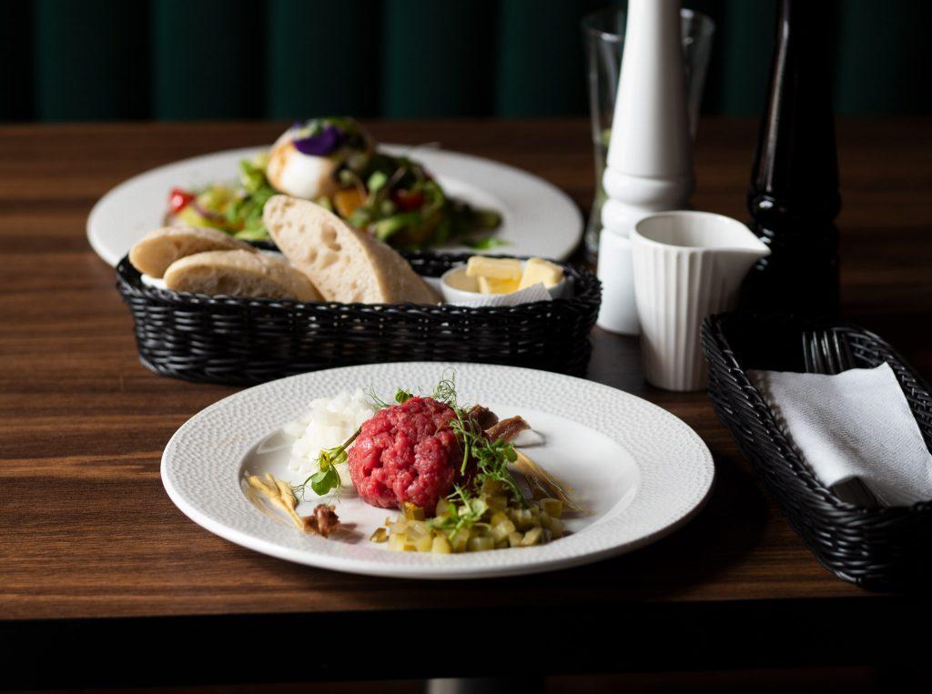 Na zdjęciu widać talerze na stole, na pierwszym tatar z dodatkami.