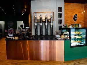 Zdjęcie przedstawia wnętrze kawiarni Kraftowa - bar, witrynę z deserami i salę.