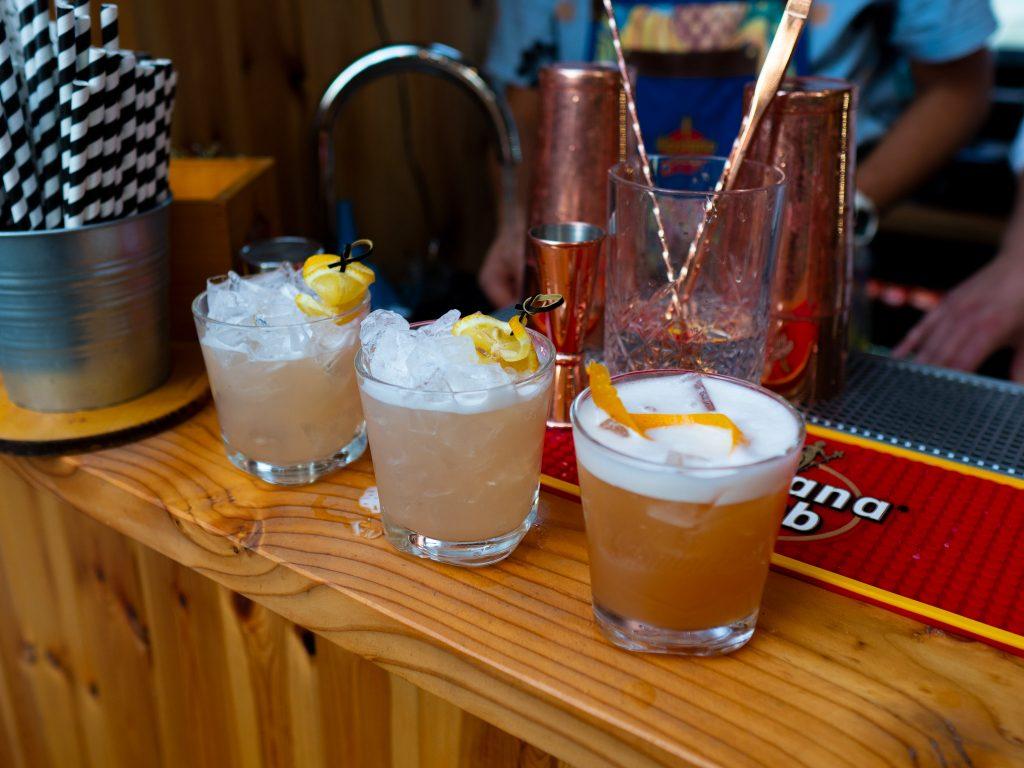 Na zdjęciu widać trzy szklanki z koktajlami stojące na barze.