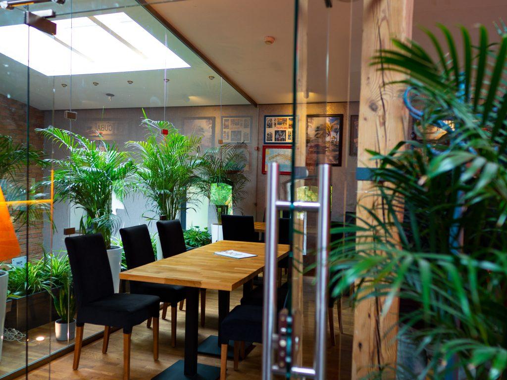 Na zdjęciu widać wnętrze restauracji Old Havana. Stolik wśród zielonych roślin i obrazki na ścianie.