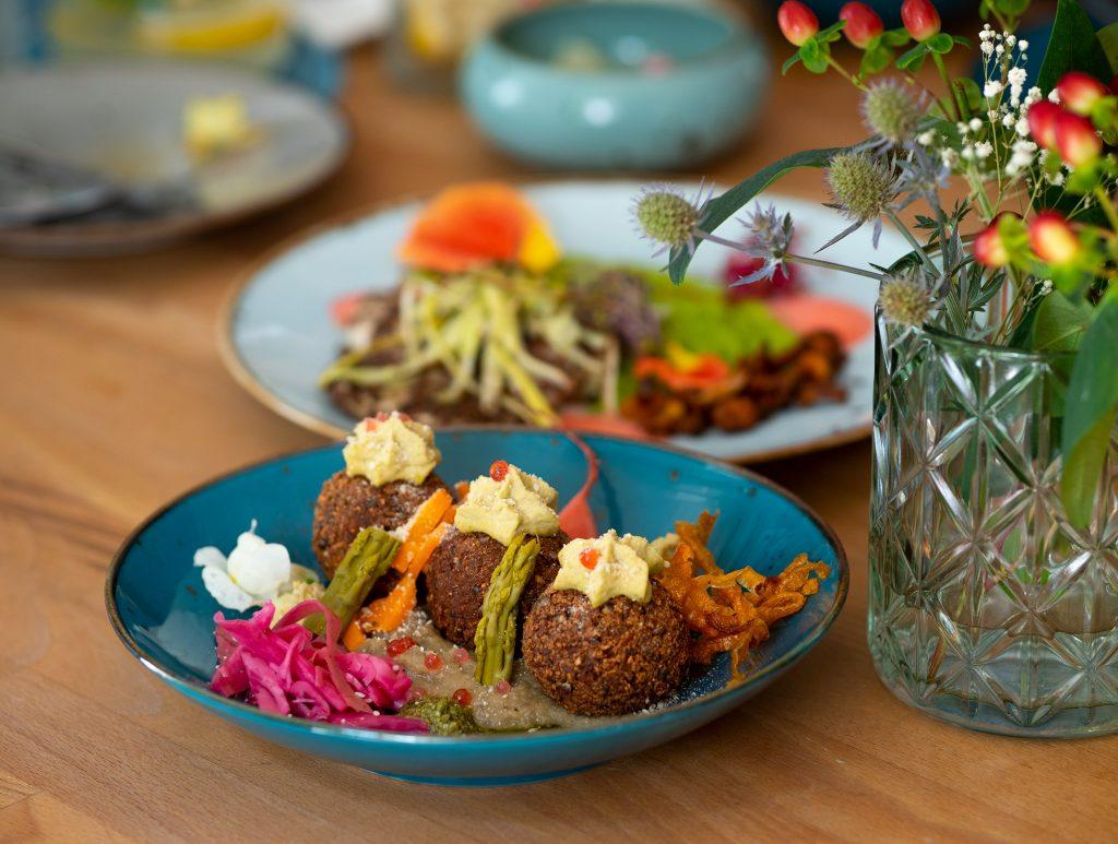Na zdjęciu widać stół w restauracji zastawiany talerzami z jedzeniem i wazon z polnymi kwiatami.