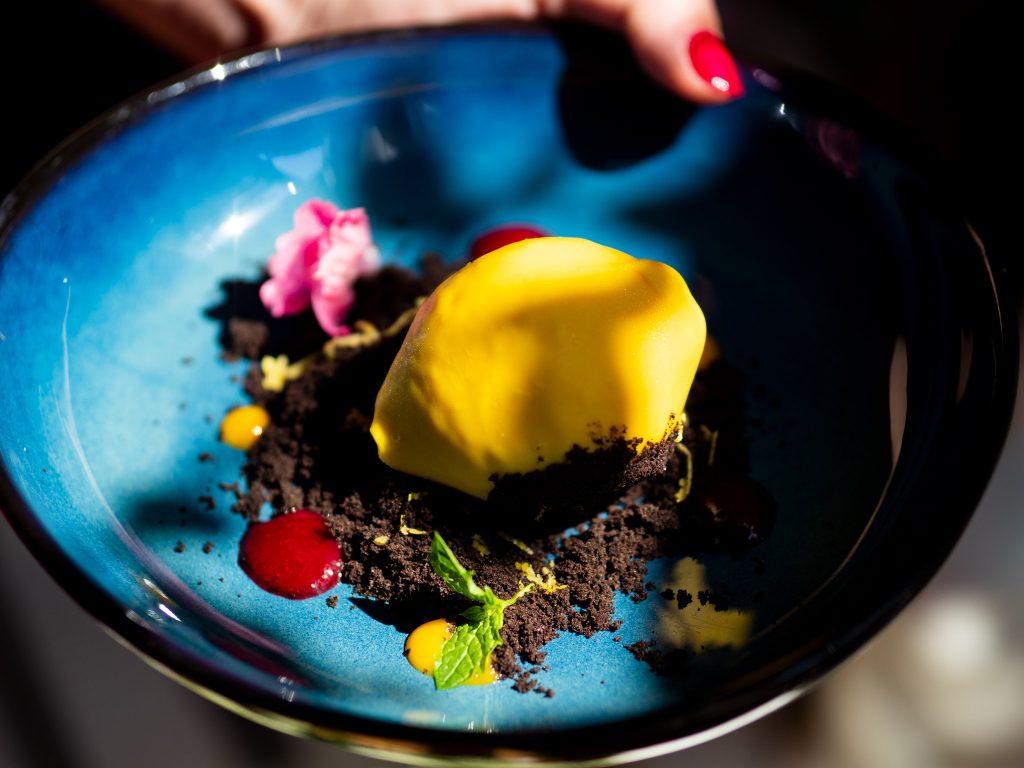 Na zdjęciu widać deser w kształcie cytryny z jadalną ziemią na niebieskim talerzu.