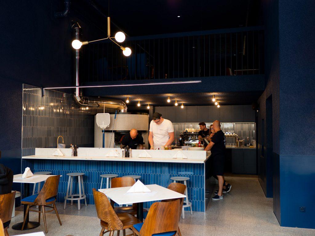 Na zdjęciu widać stoliki i stanowisko do przygotowywania pizzy lokalu Ferment.