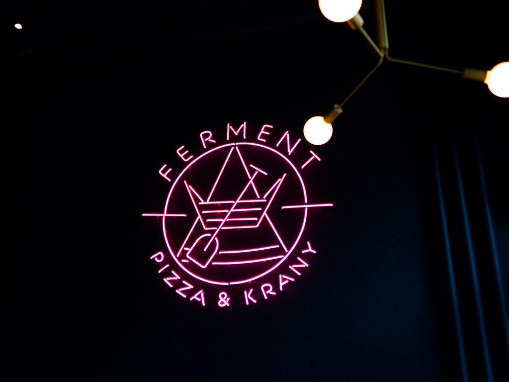 Na zdjęciu widać neon z logo pizzerii Ferment.