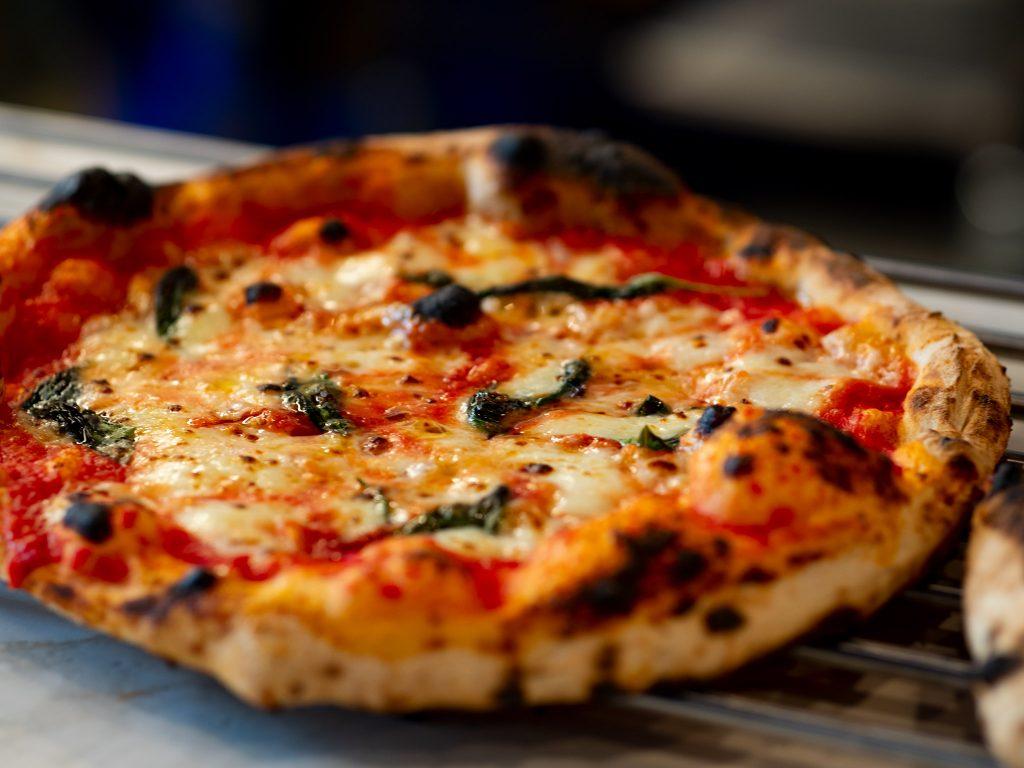 Na zdjęciu widać pizzę z wyrośniętymi brzegami.