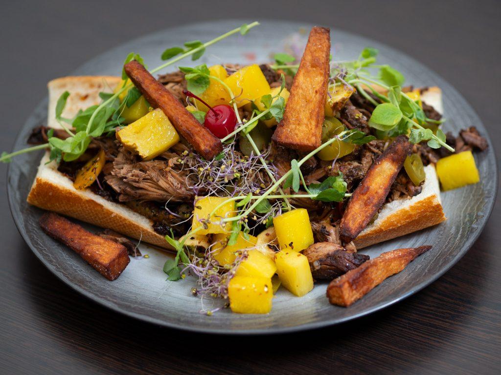 Na zdjęciu widać talerz z kanapką z szarpaną wieprzowiną i frytkami z chińskiego ziemniaka,