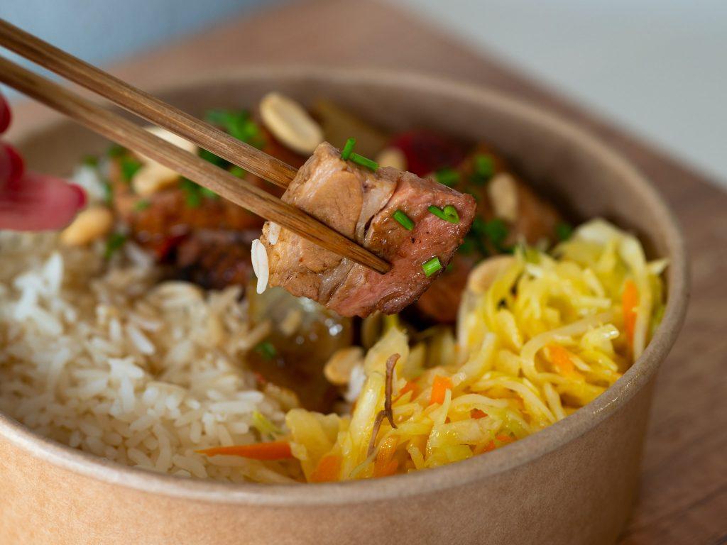 Na zdjęciu widać jednorazowe opakowanie z azjatyckim daniem - długogotowanym brzuchem, surówką i ryżem.