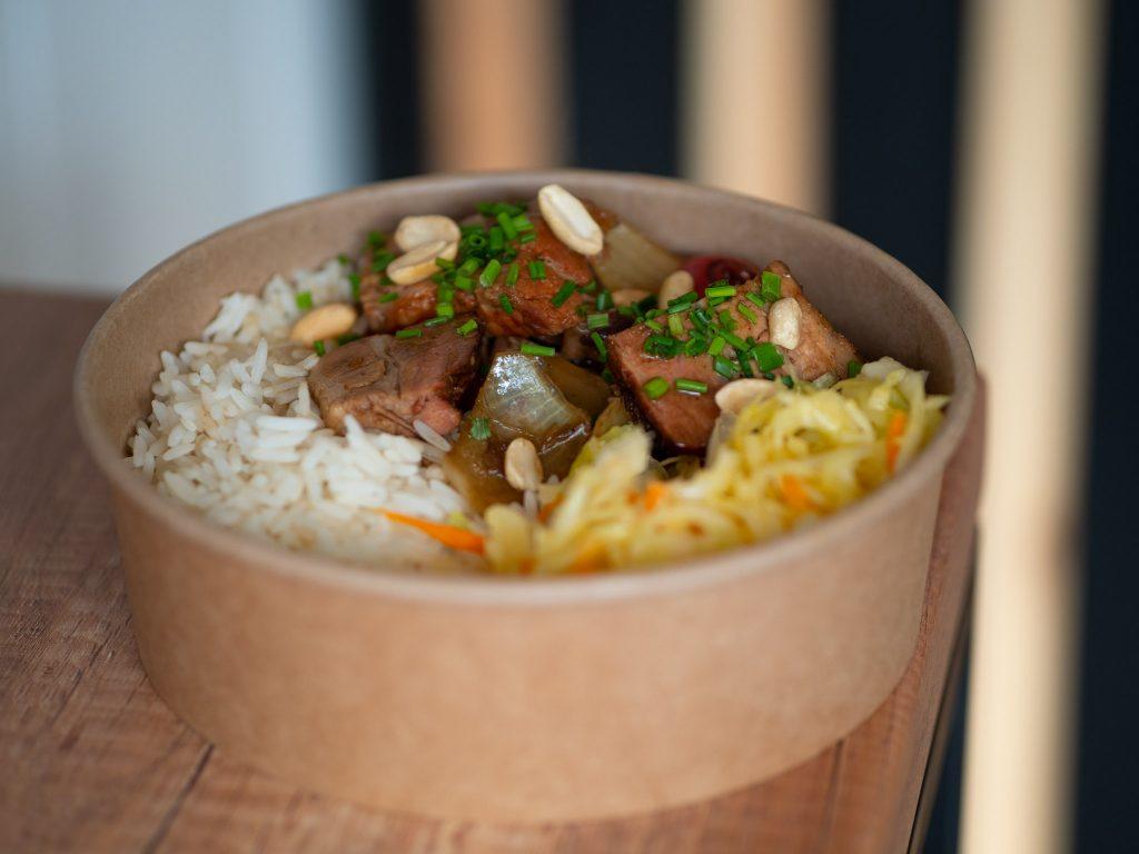 Na zdjęciu widać jednorazowe opakowanie z azjatyckim daniem - mięsem, surówką i ryżem.